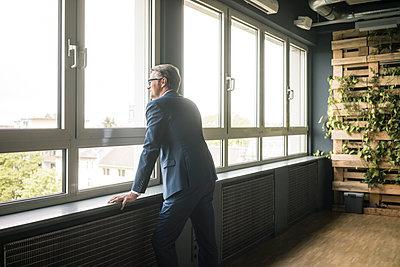 Mature businessman standing at the window in office - p300m2004720 von Joseffson