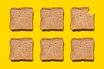 Studio shot of six slices of wheat bread against yellow background - p300m2198250 by Gemma Ferrando