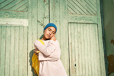 Spain, Valencian Community, Valencia. Creative portrait of a young woman in colourful clothes with a mobile phone. - p300m2276362 von Rafa Cortés