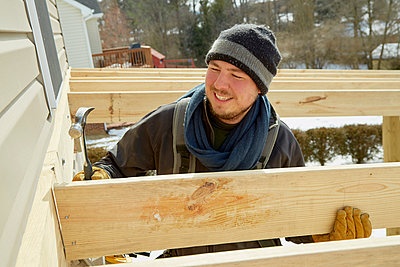 Caucasian carpenter building house extension in winter - p555m1413167 by Jeff Greenough