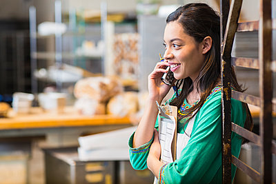 Mixed race woman working in bakery kitchen - p555m1454122 by Marc Romanelli