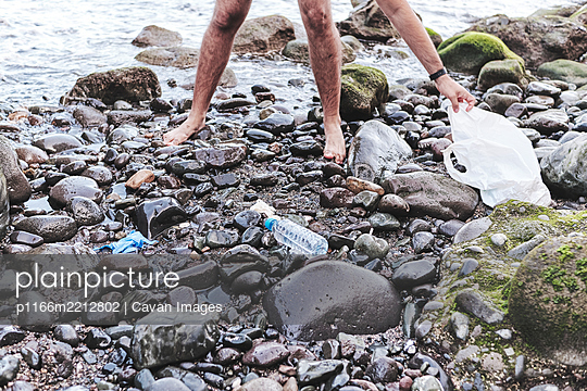Anonymous Volunteer Cleaning Beach From Plastic - p1166m2212802 by Cavan Images