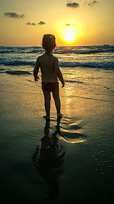 Child Looking out to Sea at Sunset  - p1019m1467954 by Stephen Carroll