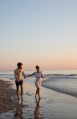 Junges Paar - Sonnenuntergang am Strand - p1212m1168723 von harry + lidy