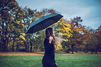 Happy young woman with umbrella walking in autumnal park - p300m1563361 by Jonathan Schöps