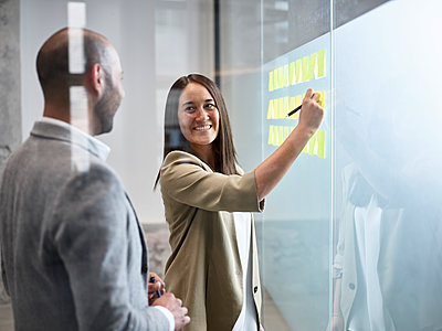 Businesswoman smiling at colleague writing on sticky notes at glass pane in office - p300m2069309 by Christian Vorhofer