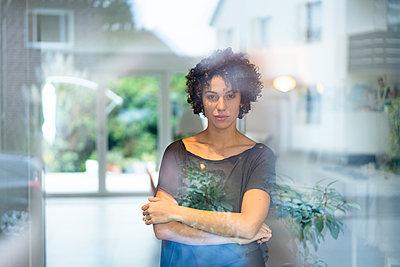 Portrait of woman standing behind window at home - p300m2080469 von Joseffson