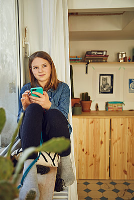Girl sitting at the window at home holding smartphone - p300m2189323 by Maya Claussen