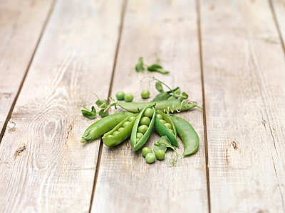 Still life of green peas in pods with pea shoots  on wooden table - p429m1062183f by Diana Miller