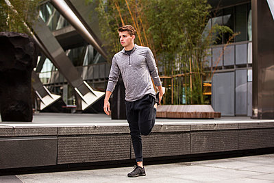 Young runner stretching on pavement, London, UK - p429m2075445 by Tom Dunkley