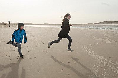 Children running across beach - p896m835040 by Sabine Joosten