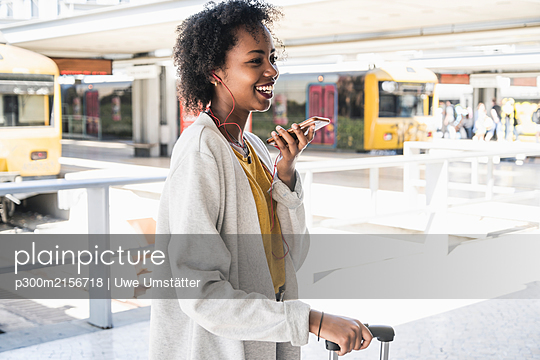 Happy young woman with earphones using smartphone at station platform - p300m2156718 by Uwe Umstätter