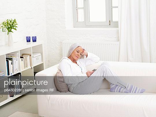 Aeltere Frau hoert Musik mit mp3-Player  - p6430228f von senior images RF