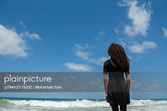 Rear view of girl standing on the beach  - p794m2115232 by Mohamad Itani