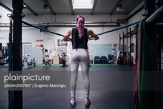 Young woman stretching arms in gym - p924m2097907 by Eugenio Marongiu