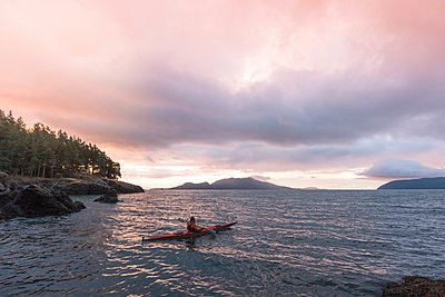 Woman kayaking on river against cloudy sky during sunset - p1166m1531344 by Cavan Images