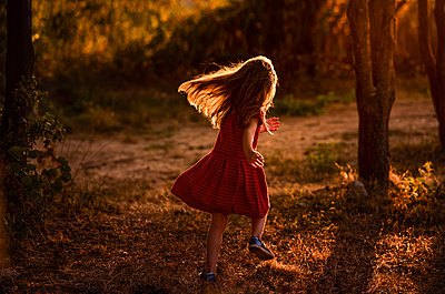 Girl runs through trees with light behind her - p1166m2137049 by Cavan Images
