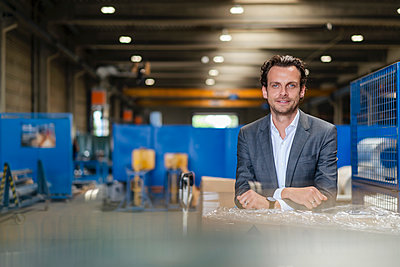 Smiling businessman leaning on cardboard box in industry - p300m2293354 by Daniel Ingold