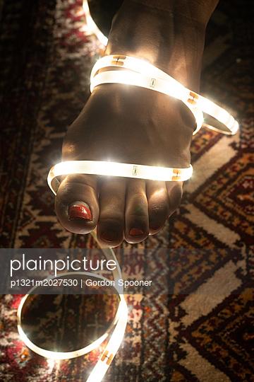Weiblicher Fuß und eine Lichterkette - p1321m2027530 von Gordon Spooner