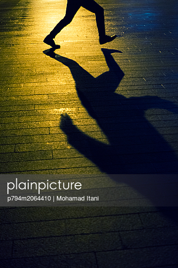 Shadow of a man running on the street at night  - p794m2064410 von Mohamad Itani