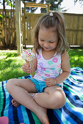 Girl eating melting messy ice cream cone on blanket in backyard - p1192m1183948 by Hero Images