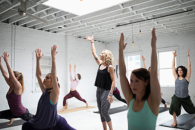Yoga instructor guiding women practicing warrior one pose in yoga class - p1192m1583340 by Hero Images