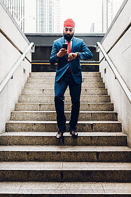 Indian businessman walking down stairs, looking at watch , holding smartphone - p300m1189513 by Giorgio Fochesato