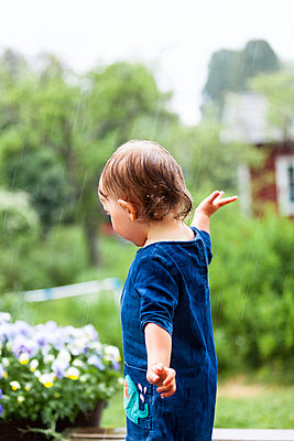 Toddler girl in rain - p312m2079585 by Anne Dillner