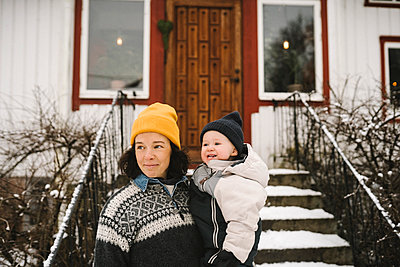 Smiling mother carrying daughter in front of house while looking away during winter - p426m2284695 by Maskot