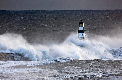 Seaham, Teesside, England; Waves crashing on lighthouse - p4429626f by Design Pics