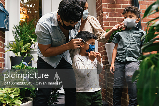 Parents putting masks on children before going out to play from home - p1166m2208543 by Cavan Images