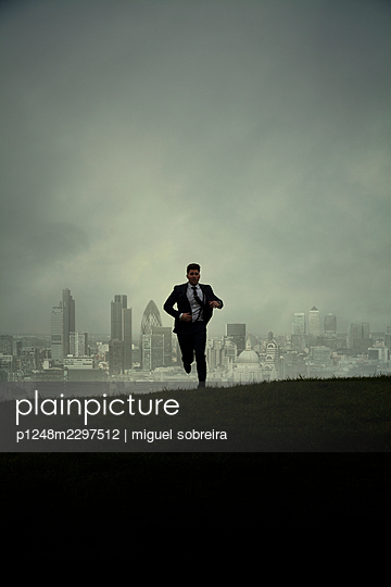 Man in suit running on grassy hilltop in the background a city - p1248m2297512 by miguel sobreira