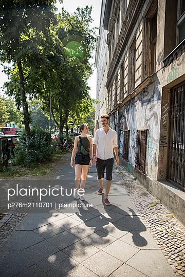 Couple walking on sidewalk in city - p276m2110701 by plainpicture