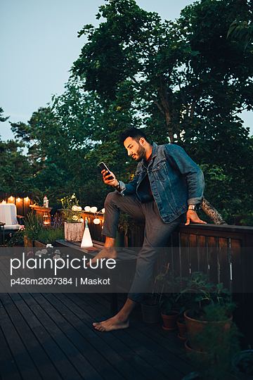 Young man using mobile phone while sitting on railing in balcony - p426m2097384 by Maskot