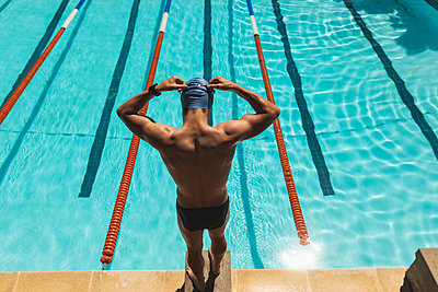 Male swimmer standing on starting block and wearing swim goggle at swimming pool - p1315m2091011 by Wavebreak