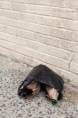Zwei Bierflaschen in Plastiktüte auf dem Boden liegend - p1340m2008462 von Christoph Lodewick