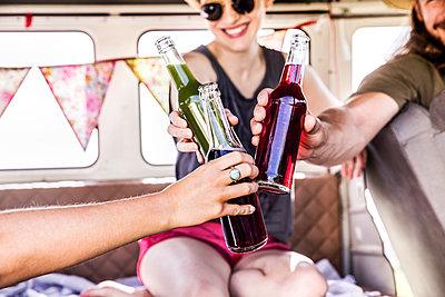 Happy friends inside van clinking bottles - p300m2070440 by Jo Kirchherr