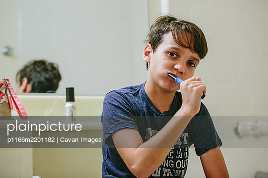 Boy brushes his teeth in the bathroom while looking at the camera - p1166m2201182 by Cavan Images