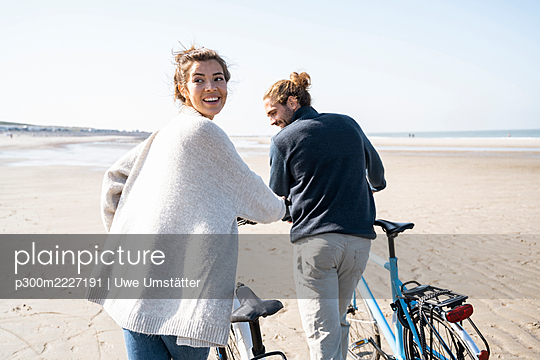 Smiling young woman walking with bicycle and boyfriend while looking over shoulder at beach against clear sky on sunny day - p300m2227191 by Uwe Umstätter
