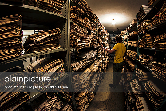 Caucasian man searching old newspapers in library archive - p555m1410902 by Maxim Chuvashov