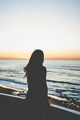 Frau blickt aufs Meer bei Sonnenuntergang - p1124m1503665 von Willing-Holtz