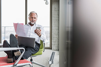 Mature businessman working on office chair with feet up - p300m1562443 by Uwe Umstätter