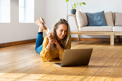 Blond woman with credit card lying down on floor while using laptop at home - p300m2277471 by Steve Brookland
