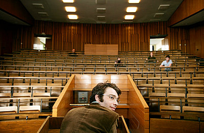 A professor looking over his shoulder in a lecture hall - p3011988f by fStop