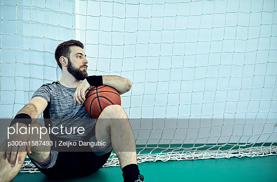 Man with basketball during break, indoor - p300m1587493 von Zeljko Dangubic