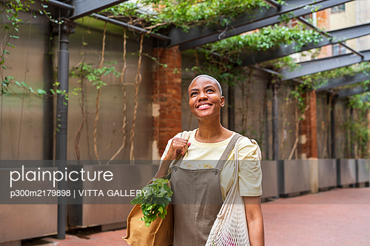 Smiling woman with grocery bag in the city looking up - p300m2179898 by VITTA GALLERY