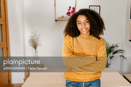 Curly hair woman standing with arms crossed at home - p300m2256665 by Tania Cervián