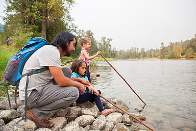 Father and daughters fishing with sticks at lakeside - p1023m1542507 by Monashee Alonso