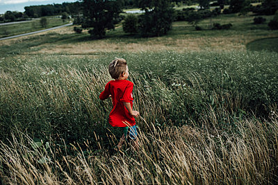 Rear view of boy running on grassy field - p1166m2001059 by Cavan Images