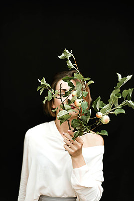 Portrait of woman with a branch of apples against black background - p1166m2111982 by Cavan Images